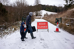 © Licensed to London News Pictures. 08/02/2021. Surrey, UK. A father and son walk past a closed road sign at the bottom of Box Hill as blizzard and treacherous conditions in the South East continue. Storm Darcy has hit the South East again with more yet snow and freezing temperatures today. The Met Office have issue numerous weather warnings for heavy snow and ice with disruption to travel, power cuts and possible stranded vehicles as the bad weather continues.  Photo credit: Alex Lentati/LNP