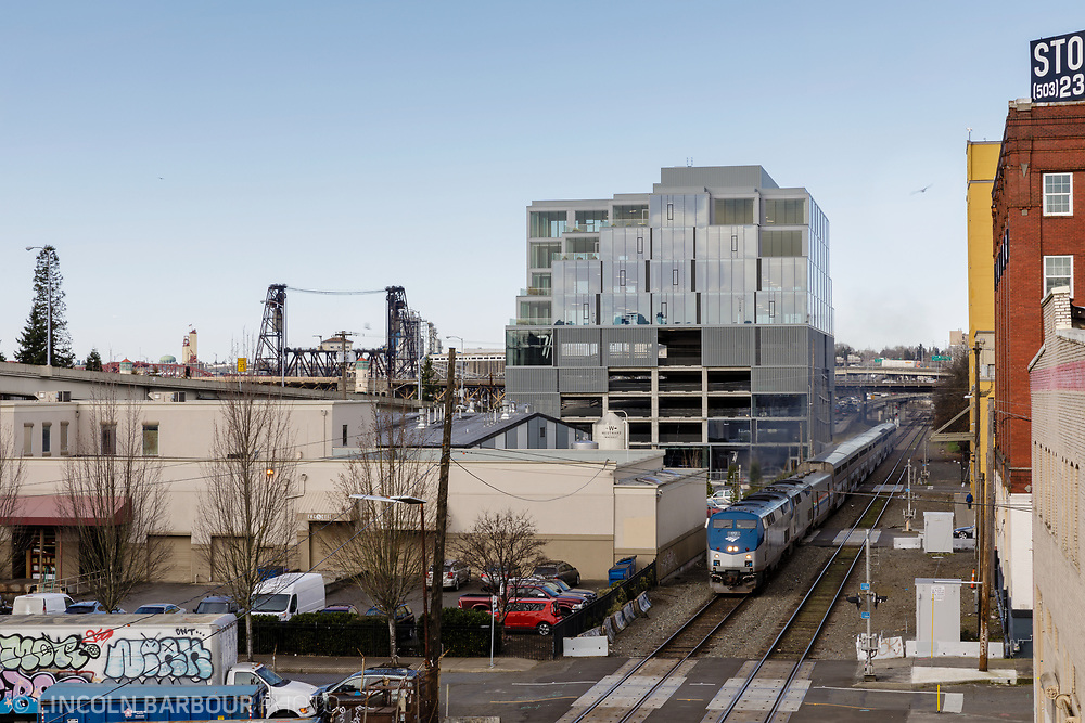 The new 7 Stark Building stands over the train as it passes through the industrial east side of Portland, Oregon.