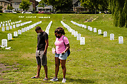 """15 AUGUST 2020 - MINNEAPOLIS, MINNESOTA: People bow their heads in prayer in the """"Say Their Names"""" cemetery, honoring people of color killed by police near the George Floyd Memorial in Minneapolis. Floyd, an unarmed Black man, was killed by Minneapolis police officers of May 25 in front of Cup Foods, a convenience store at the intersection of 38th and Chicago Ave. His killing sparked a week of violent protests across the country. The intersection where he was killed is still closed and has become an unofficial memorial visited by hundreds of people every day. Saturday, more than 100 people gathered at the memorial to demand the city preserve the memorial. The city of Minneapolis had planned to start reopening the intersection as soon as Monday Aug. 17, but delayed those plans indefinitely on Friday, Aug. 14. City residents have created a """"George Floyd Zone"""" at the intersection. They're demanding the recall of Hennepin County Attorney Mike Freeman, requiring Minneapolis police officers have their own private liability insurance, and the allocation of funds for businesses and residents in the community. The city is considering officially renaming Chicago Ave. between 37th and 39th """"George Floyd Jr. Place.""""     PHOTO BY JACK KURTZ"""