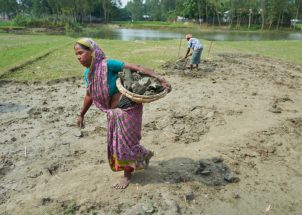 In order to raise her home a few inches, Zahura Khatun carries dirt in a basket in West Fasura, a village on an island in the Brahmaputra River in northern Bangladesh. Severe flooding in August 2017 destroyed the island's crops but RDRS Bangladesh, a member of the ACT Alliance, provided emergency cash grants to vulnerable island families so they could reestablish their household economies and restart their lives.