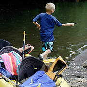 KAUAI, HI, July 14, 2007: A young boy stops to skip rocks while kayaking the Hanalei River with his family en route to the Hanalei National Wildlife Refuge on the North Shore of Kauai (Photograph by Todd Bigelow/Aurora)