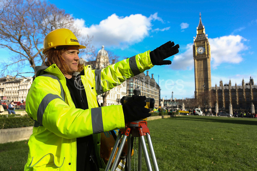 Greenpeace pretends to frack with their own mock fracking company Frack&Go and drilling rig in Parliament Square, Central London, 9th February 2016. As part of the mock drilling a number of activists dressed as land surveyors inspect the green for potential future fracking.  Greenpeace wants to highlight that fracking is a highly polluting and destructive way of extracting gas and to push for increased awareness of this, they set up their own rig outside Parliament without prior permission.