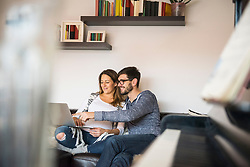 Pregnant woman and husband with laptop on sofa, Munich, Germany