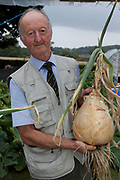 Peter Glazebrook with a giant onion. He has held eight world records in his time but is currently holder of only two with heaviest parsnip and longest beetroot, 12lb and 21ft. respectively. Giant vegetable growing is not a hobby for the faint hearted. The growers have to tend to the vegetables almost every day (including Christmas) spending up to 80 hours a week, tending, nurturing, growing and spending thousands on fertilisers, electricity and green houses. The reward is to be crowned world record holder of largest, longest or heaviest in class, cabbages weighing in at 100lb, carrots stretching 19 ft and pumpkins tipping the scales at 800lb. it's a competitive business though and global; some times the record may stand for only hours before a fellow competitor, somewhere,  knocks a grower off the coveted spot.