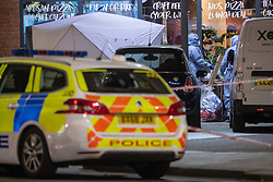 © Licensed to London News Pictures. 23/04/2021. London, UK. Forensic investigators gather evidence next to a tent on Barking Road in Canning Town following the fatal stabbing of a 14-year-old boy. Police were called at 15:56 BST on Friday, 23 April to reports of an assault in Barking Road, E16. Metropolitan Police officers attended with medics from the London Ambulance Service and the London Air Ambulance. They found a 14-year-old male who had been stabbed. He was pronounced dead shortly after 16:30 BST. Photo credit: Peter Manning/LNP
