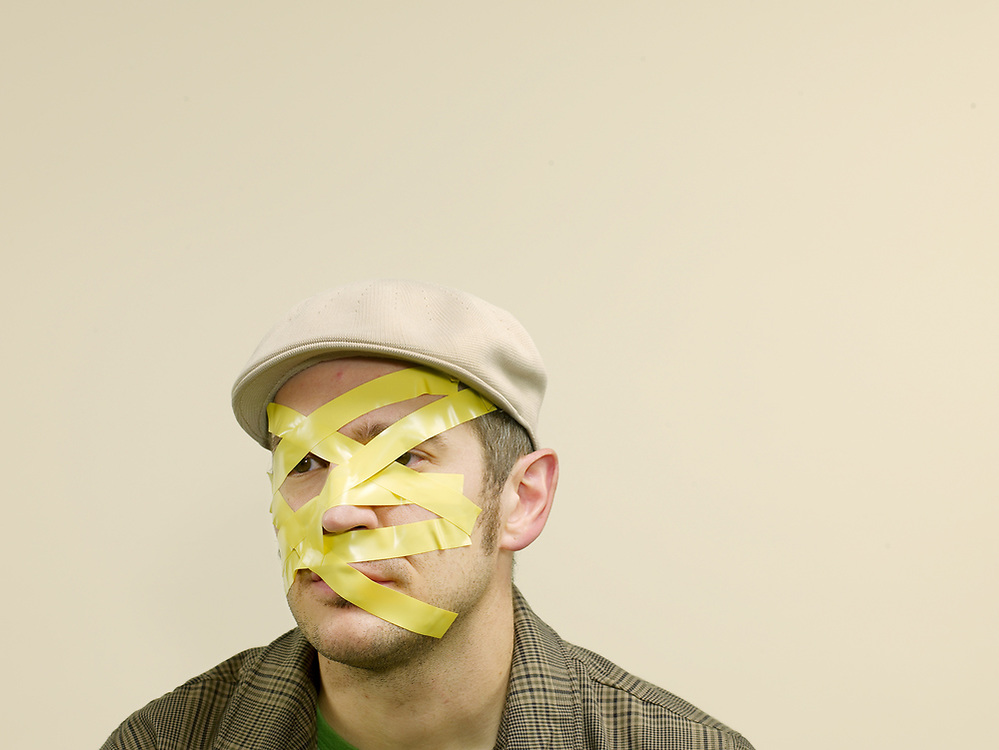 30 something male with yellow electric tape on face
