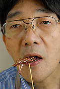 """Shoichi Uchiyama eating a locust.Tokyo resident Shoichi Uchiyama is the author of """"Fun Insect Cooking"""". His blog on the topic gets 400 hits a day. He believes insects could one day be the solution to food shortages, and that rearing bugs at home could dispel food safety worries."""