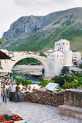 View along the river of the old reconstructed bridge. The busy old market bazaar street Kujundziluk with lots of tourist craft and art shops and street merchants. Historic town of Mostar. Federation Bosne i Hercegovine. Bosnia Herzegovina, Europe.