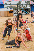 A group of girls make a video for social media while playing around the Latitude sign in the Arena - The 2018 Latitude Festival, Henham Park. Suffolk 13 July 2018