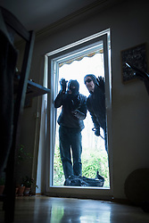Two burglars peeking through terrace door of house