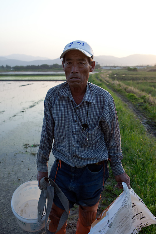 Portrait of a farmer who is seeding rice in a field located at the outskirts of Gyeongju. Gyeongju, South Korea, Republic of Korea, KOR, 20th of May 2010.