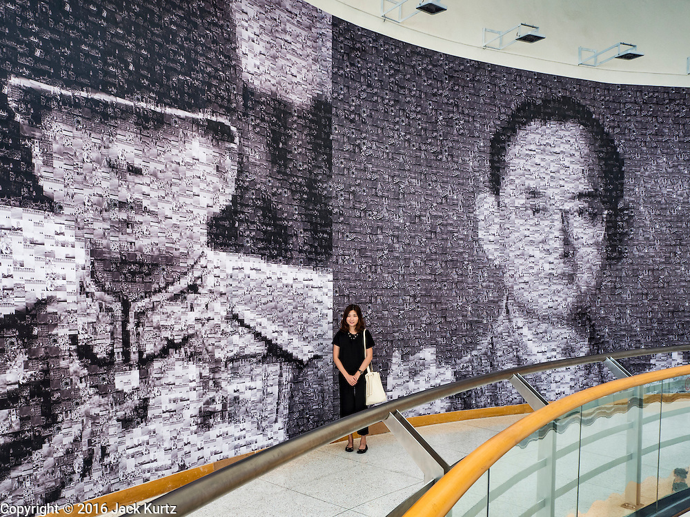 """06 NOVEMBER 2016 - BANGKOK, THAILAND: A Thai woman stands in front of large mosaic photos of Bhumibol Adulyadej, the late King of Thailand at the Bangkok Art and Culture Centre. The Royal Photographic Society of Thailand with the Bangkok Art and Culture Centre and Thai Beverage Public Company Limited are hosting a photography exhibition to commemorate the late Thai King Bhumibol Adulyadej. The """"In Remembrance of His Majesty King Bhumibol Adulyadej"""" Photography Exhibition is dsiplaying 89 photographs by 89 photographers honoring King Bhumibol Adulyadej's legacy. The King was an avid photographer was usually seen with a camera in his hands. The exhibition will be on display until 27 November 2016 on the Curved Walls on the 3rd - 5th floor, Bangkok Art and Culture Centre.     PHOTO BY JACK KURTZ"""
