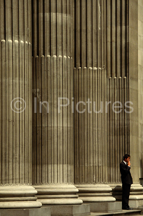 A young office worker wearing a dark suit stands outside his place of work in a sunny Trinity Square in the City of London, for a quick cigarette break. Puffing guiltily on his fag n the pavement outside beneath the huge supporting pillars of this financial institution. He draws on his cigarette, a sign of his addiction and enjoyment of taking a five or ten-minute pause from his office job. A report showed smokers each lose an average of 30 minutes a day from their workplaces to satisfy their habit. The average smoker takes at least three breaks from the office, each lasting around 10 minutes, research for the Benenden Healthcare Society found. The healthcare group estimates that 290,000 working days are being lost by people leaving their office to smoke.