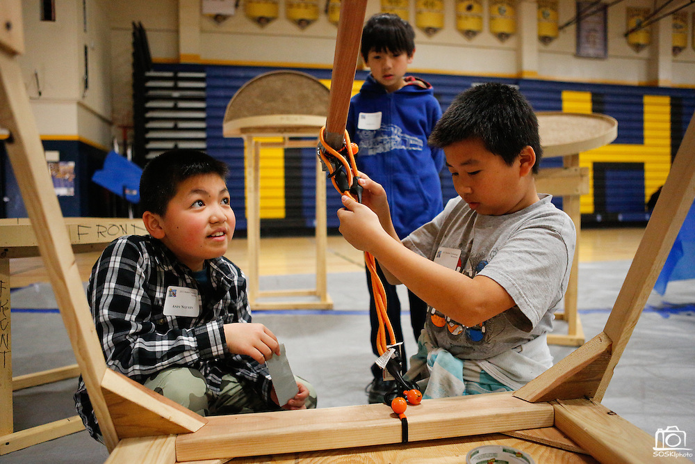 Andy Nguyen, 10, and Garry Zeng, 10, of Rose Elementary School's 4th through 6th grade GATE class adjust elastic bands on their catapult, which will be used during the San Jose Tech Museum's Tech Challenge, as Andy Vu, 11, watches during the MUSD Student Technology Showcase at Milpitas High School in Milpitas, California, on March 2, 2013. (Stan Olszewski/SOSKIphoto)