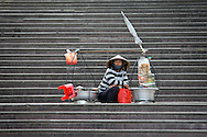 Vendor with her yoke and baskets waits for customers on the market square steps in Dalat City, Lam Dong Province, Vietnam, Southeast Asia