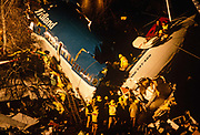 Using ladders and ropes during a rescue operation, Fire Brigade crews enter the floodlit broken air frame of a British Midland Airways Boeing 737-400 series jet airliner which lies on an embankment of the M1 motorway at Kegworth, near East Midlands Airport in Leicestershire, England. On the night of 8th January 1989, flight 92 crashed due to the shutting down of the wrong, malfunctioning engine. Attempting an emergency landing, 47 people died and 74 people, including seven members of the flight crew, sustained serious injuries. We see the aircraft's tail snapped upright at ninety degrees. Here perished most of the passenger fatalities. The devastation was hampered by woodland and the fire fighters are attempting to rescue survivors or extract those killed in this air disaster that proved one of Btitain's worst.