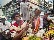"""22 OCTOBER 2015 - YANGON, MYANMAR: A Hindu man in Yangon perfumes the air with incense during a Navratri procession to the Sri Kali Temple. Navratri, literally """"nine nights"""" is a Hindu festival devoted to the Goddess Durga. Navratri festival combines ritualistic puja (prayer) and fasting. Navratri in India follows the lunar calendar and is celebrated in September/October as Sharad Navratri. It's widely celebrated in countries in Southeast Asia that have large Hindu communities, including Myanmar (Burma). Many of Myanmar's Hindus are descendants of Indian civil servants and laborers who came to Myanmar when it was the British colony of Burma.   PHOTO BY JACK KURTZ"""
