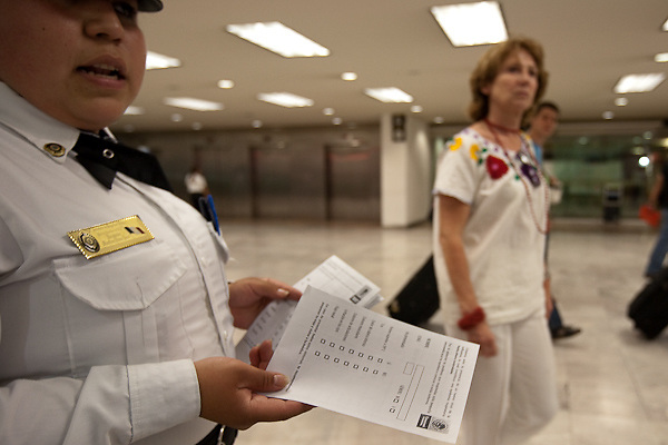 26 April 2009,  Mexico City, Mexico---   A  police officer hands out health surveys at the Mexico City airport. The government continues to allow people to arrive and leave freely. But thousands of police and soilders have been dispatched to the airport to give out surveys, provide security, and hand out surgical masks. --- Image by © Trevor Snapp
