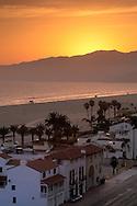 Sunset over coastal mountains and homes along sand beach at Santa Monica, Los Angeles County, California