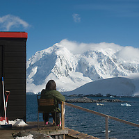 A caretaker sits outside the mai hut at Port Lockroy, an abandoned British Science base on Goudier Island, Antarctica that has been restored as a museum. Mountains on Anvers Island are in the background.
