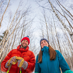 A man and woman snowshoeing in a forest of paper birch trees at Loon Echo Land Trust's Bald Pate Mountain Preserve in South Bridgton, Maine.