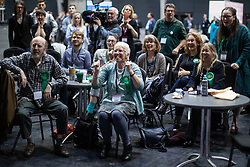 © Licensed to London News Pictures . 26/05/2019. Manchester, UK. Green Party supporters cheer as they watch results on TV screens in the counting hall . The count for seats in the constituency of North West England in the European Parliamentary election , at Manchester Central convention centre . Photo credit: Joel Goodman/LNP