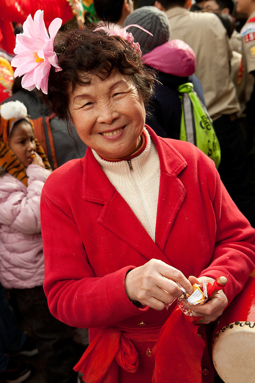 A Chinese-American woman participating in the parade opens a fortune cookie.