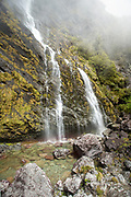 Scenic landscape with a waterfall and a rocky cliff, Routeburn Track, South Island, New Zealand