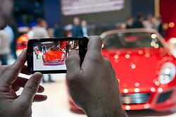 Visitor photographing Ferrari SA Aperta car  with camera phone at Paris Motor Show 2010