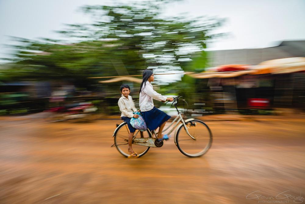 Children cycling through the village after a rain shower, Krong Kampong Chhnang, Tonle Sap, Cambodia
