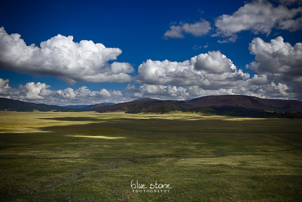 A southwestern caldera, an open meadow that was formed by volcanic activity, with a pattern of shadows from the clouds.