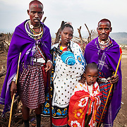 Wilson's wedding day...The wedding photograph, Wilson on the right with his wife and best man. With him is a young relative and his wife is carrying their small child on her chest. Wilson and his wife has been seeing each other for 5 years and have a baby together but today is their official wedding day.. .It is mainly Maasais who live in the Loita Hills up above the Serengeti plains. They live in small villages and communities called bomas and live mainly of raising and selling live stock such as cattle and goats. Its a very remote region in Kenya, hard to get to without a four wheel drive with very little infrastructure and up till 2010 no mobile phone network. The Maasais are well known though out Kenya and the world for their colorful clothing and their way of keeping their old traditions alive.
