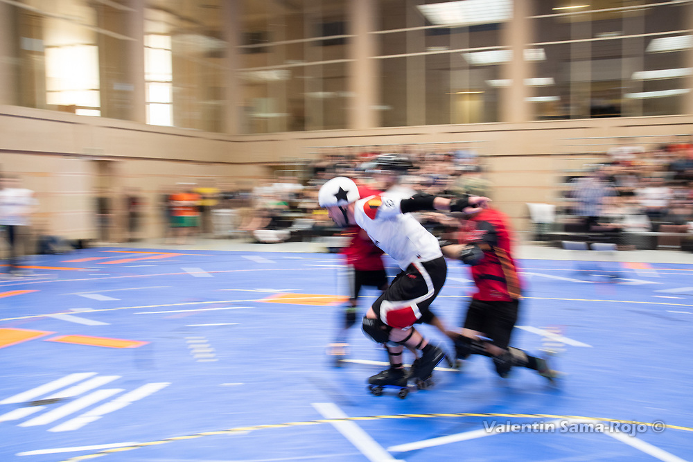 The jammer of Team Belgium jumping between two player of Team Spain during the MRDWC2018 in Barcelona, Spain.