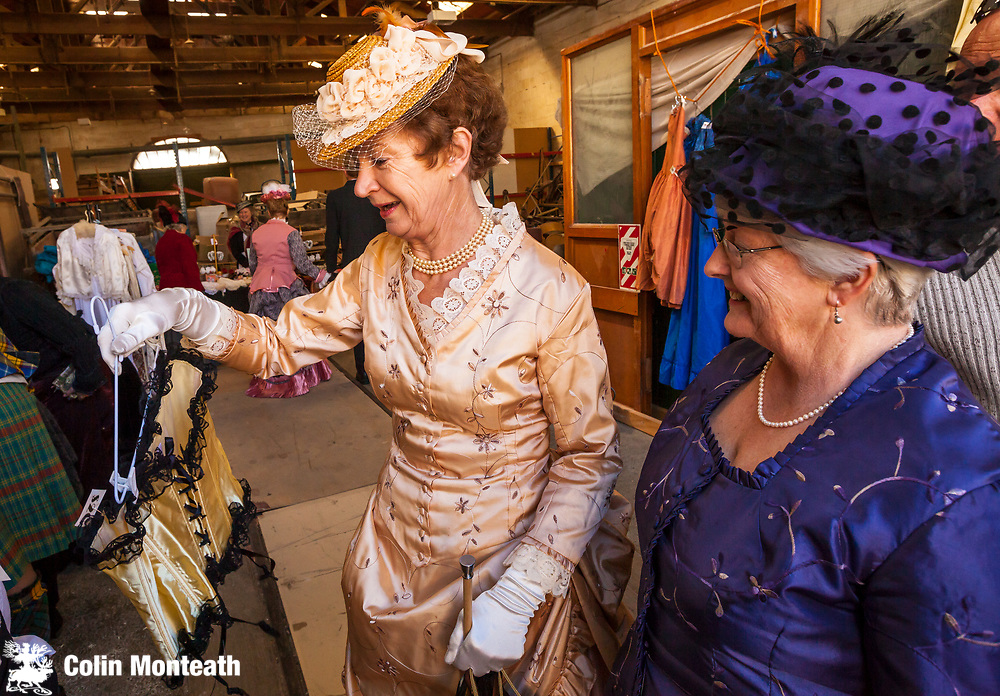 Ladies in Victorian dresses find old corsets in clothing stall, Victorian festival, historic precinct, Oamaru, Otago