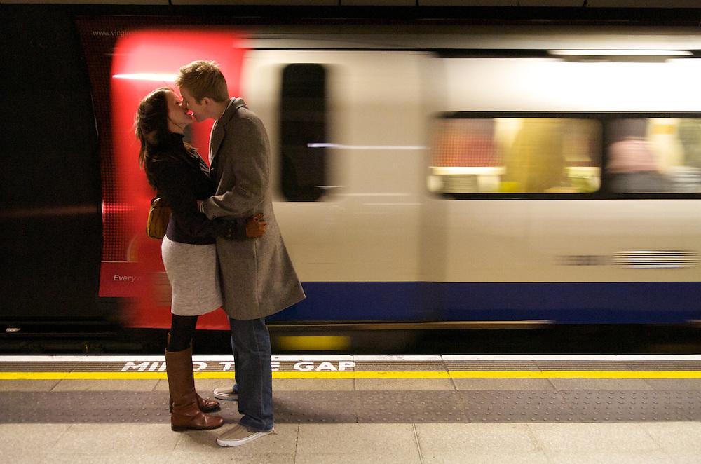 A couple snogs on the London Bridge tube station platform.