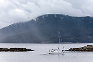 A small sailboat readies to leave Vesuvius on Saltspring Island, British Columbia.  The clouds are rolling over Maple Mountain (on Vancouver Island) bringing rain to Stuart Channel and Vesuvius Bay.