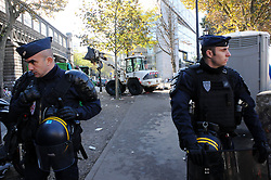 "French anti-riot policemen stand in front of migrants near the Jaures and Stalingrad metro stations, in northern Paris, France, on October 31, 2016, during a police operation aiming at a future evacuation of a migrant camp. An operation of ""administrative control"" was underway on early October 31 in the Jaures/Stalingrad quarter before a future evacuation, whose date has not yet been set, according to a police source. The makeshift camp on the outskirts of the 10th and 19th arrondissements in the north of the capital numbers today 2,500 people, according to the City of Paris. Photo by Alain Apaydin/ABACAPRESS.COM"