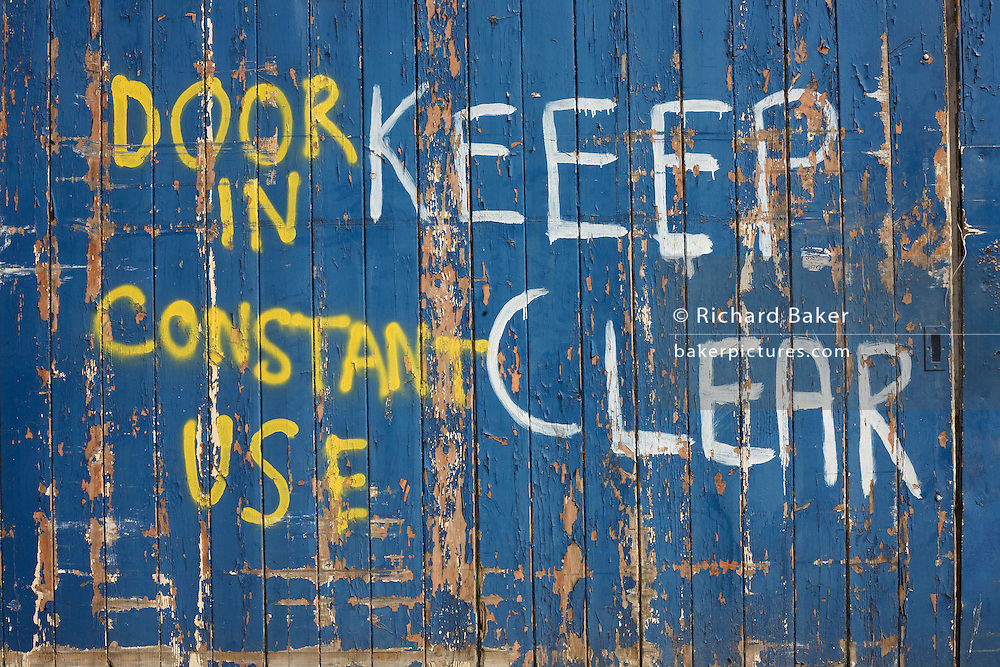 """The words """"keeep (mis-spelled) clear .. door in constant use"""" has been painted by hand on an entrance to a now derelict building that is soon to be developed into new apartments. Peeled blue gates has been rubbed away to reveal the old wood in the once-industrial Tetley Street near Bradford city centre, Yorkshire."""