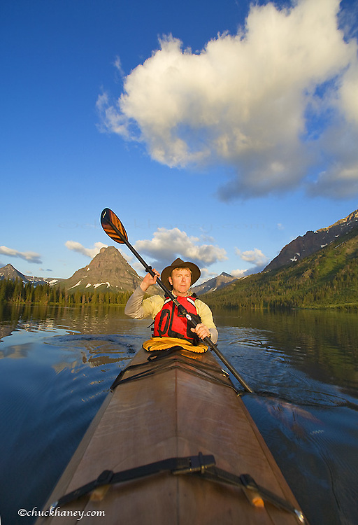 Paddling a sea kayak on a calm Two Medicine Lake in Glacier National Park in Montana model released