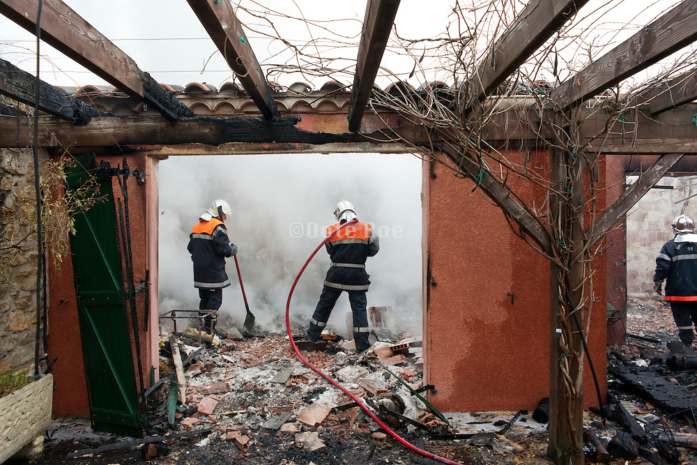 total loss burned out house with firefighters putting out the still smoldering remains