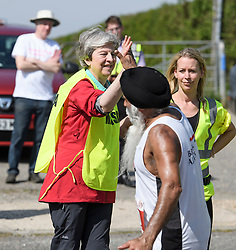 © Licensed to London News Pictures. 19/04/2019. Maidenhead, UK. Prime Minister THERESA MAY gives a high five as she helps out as a marshal at the Maidenhead Easter 10 run in her constituency of Maidenhead in Berkshire. Parliament currently on Easter recess after an extension to Article 50 was granted by the EU. Photo credit: Ben Cawthra/LNP