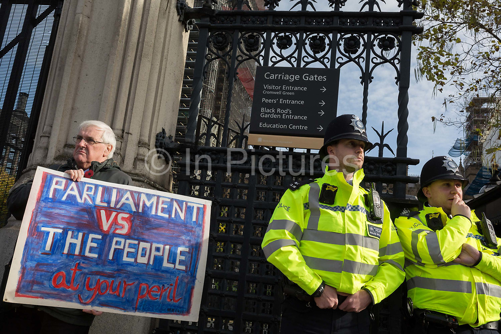 On the day that the EU in Brussels agreed in principle to extend Brexit until 31st January 2020 aka Flextension and not 31st October 2019, a Brexiters stands next to a police officer beneath the railings outside parliament with a placard warning of a confrontation between the People and Parliament, on 28th October 2019, in Westminster, London, England.