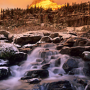 Mount Clements and a flowing stream in the morning alpenglow during the fall in Glacier National Park, Montana.