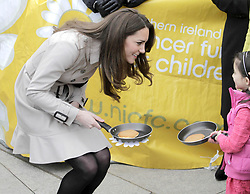 Kate Middleton flips a pancake with Ellie Tang, 6, at a display by the charity Northern Ireland Cancer Fund for Children outside Belfast City Hall during their visit to Northern Ireland.