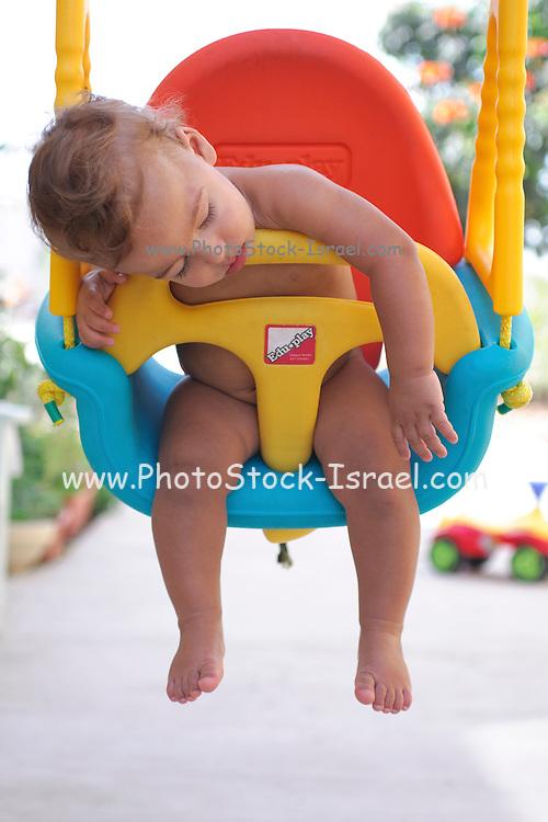 Baby boy fast asleep on a swing