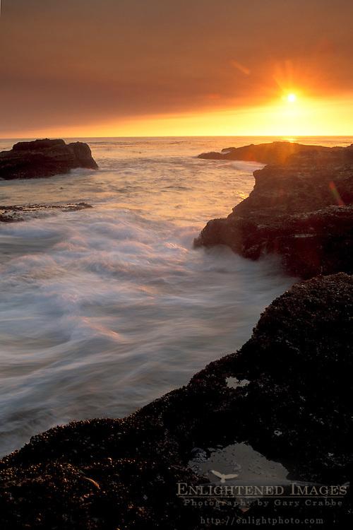 Golden sunset and ocean waves break on coast rocks, Point Lobos State Reserve, near Carmel, Monterey County, California