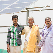 CAPTION: Bhageerat Rai, the landowner of the plot where the OORJAgram Rural Enterprise Zone is being constructed, stands proudly flanked by his son (right) and grandson (left). Behind them rises the first solar panel to be completed at the site. LOCATION: Diara Rasulpur, Saran District, Bihar, India. INDIVIDUAL(S) PHOTOGRAPHED: From left to right - Subodh Ray, Bhageerat Rai and Jeetan Rai.
