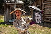 An actress in period costume conducts visitors on the Chinatown Tour in Barkerville Historic Town & Park, in British Columbia, Canada. Historically the main town of the Cariboo Gold Rush, Barkerville is now the largest living-history museum in Western North America. The town was named after Billy Barker from Cambridgeshire, England, who struck gold here in 1861, and his claim became the richest and the most famous. This National Historic Site nestles in the Cariboo Mountains at elevation 1200m (4000ft), at the end of BC Highway 26, 80 kilometres (50 mi) east of Quesnel. Gold here was first discovered at Hills Bar in 1858, followed by other strikes in 1859 and 1860. Wide publication of these discoveries in 1861 began the Cariboo Gold Rush, which reached full swing by 1865 following strikes along Williams Creek. To license this Copyright photo, please inquire at PhotoSeek.com.