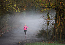 © Licensed to London News Pictures. 16/12/2018. London, UK. A woman jogging through mist covered hills at sunrise at Parliament hill on Hampstead Heath, on a cold winter morning.  Large parts of the UK have experienced snowfall as storm Deidre brings freezing temperatures. Photo credit: Ben Cawthra/LNP