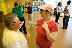 Woman Day Service users with learning disability taking part in dance class with Care Assistant joining in the activity,